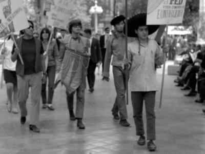 """Actores del Teatro Teknos promocionando la obra """"El pequeño Malcolm y su lucha contra los eunucos"""" por las calles de Santiago. Santiago, 1967."""